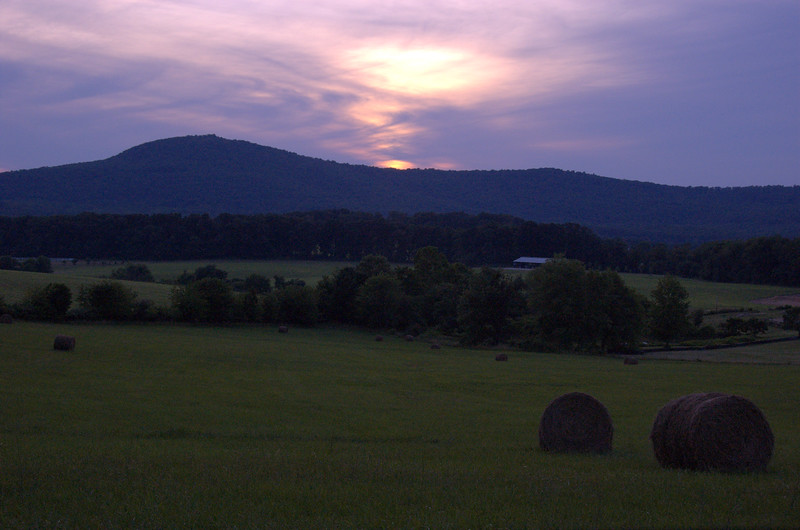 June 24 <br /> <br /> Bales of hay and a sunset! <br /> <br /> Well, of sorts... (the sunset i.e.)  We drove up to Sugarloaf Mountain to catch the sunset, and at this hour, the best vantage point is what you see. Had to stay in the car for this photo, as the dogs on the nearby farms raced out to shoo us off...