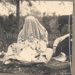 This is my favorite mother and child shot in my collection of hidden mothers. She's under the blanket using the striped fabric as the backdrop for this picture.  I think it was taken by an older sibling (and an inexperienced photographer). Notice how the father's head is cut off and just the back end of the horse is visible.