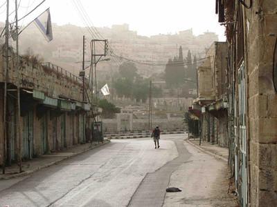 En bosetter vandrer ned Shuhada gaten i Hebron langs stengte palestinske butikker. Gaten, som ligger midt i byen, er stengt for palestinere. -- by Ingvild Skogvold