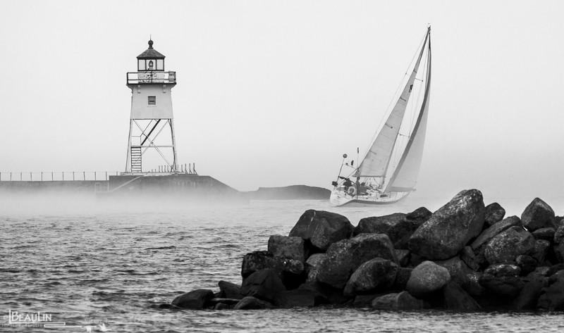 Sailboat leaving Grand Marais Harbor and venturing into foggy Lake Superior (Gichigami)
