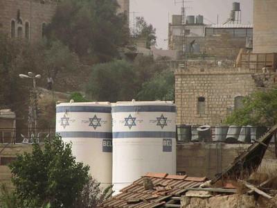 Sammenlign bosetternes vanntanker (forgrunnen) med de palestinske (bakgrunnen til høyre). Israelske bosettere lider ikke av vannmangel.  -- by Ingvild Skogvold
