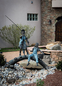 Sunday 6 April 2014: WATERLESS FISHING  Kathy and I were driving around a neighborhood close to where we live and happened upon this incredible, full-sized bronze, of a young boy and girl on a log, fishing. Obviously, this piece of art is intended to traverse a man-made stream coming from a fountain in the front of the house, but because of the still-cold nights we are having, the home owner hasn't seen fit to fill it with water. I love the whole idea of the display and will surely go back and see it and shoot it again when the weather warms and the water is added.