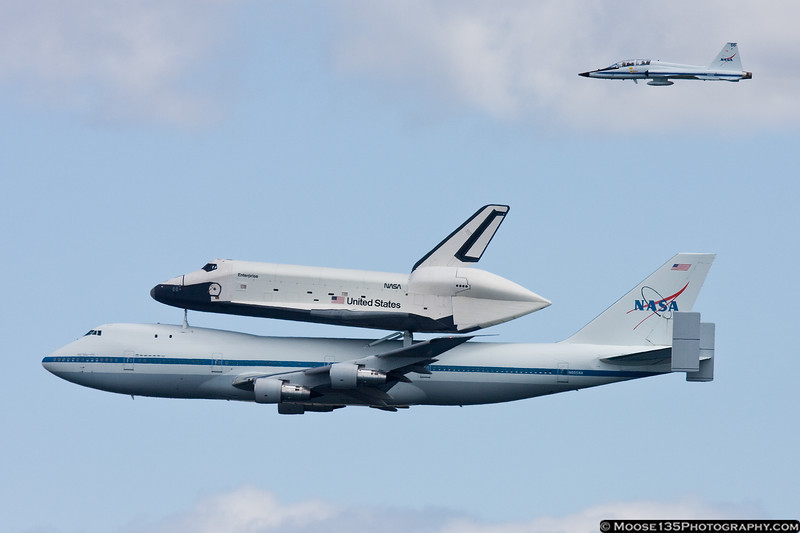 April 27 - Space Shuttle Enterprise on the 747 Shuttle Carrier Aircraft, with T-38 chase plane, arrives at Kennedy Airport.