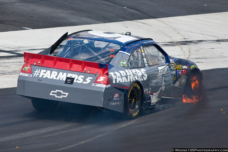 June 10 - After hitting the wall, Kasey Kahne retires his flaming car out of the Pocono 400.