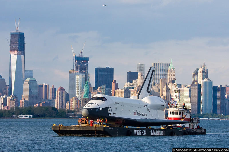 June 3 - Crews prepare to dock Space Shuttle Enterprise in Bayonne, NJ on the way to the USS Intrepid, with the Statue of Liberty, new World Trade Center, and the rest of lower Manhattan in the background.