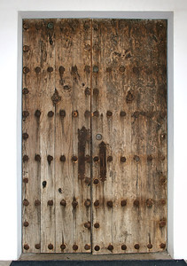 An old double door with heavy brass nails and hasp, An old double door with heavy brass nails and hasp