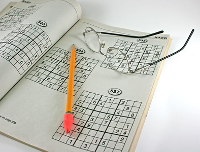newspaper puzzles, eyeglasses and pencil on an isolated background, newspaper puzzles, eyeglasses and pencil on an isolated background