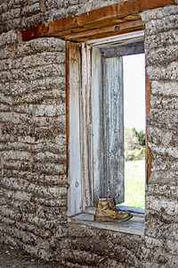 the inside of a pioneer sod house with a shoe in the window, the inside of a pioneer sod house with a shoe in the window