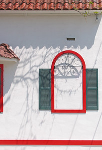 a false window in red with green shutters on stucco, a false window in red with green shutters on stucco