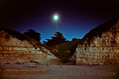 Bonny Doon Beach Moonrise over cliffs -- cliffs and trees are lit by last rays of sunset(behind photographer) and the moon is shown top-center of frame, blurred by long exposure. (1993)