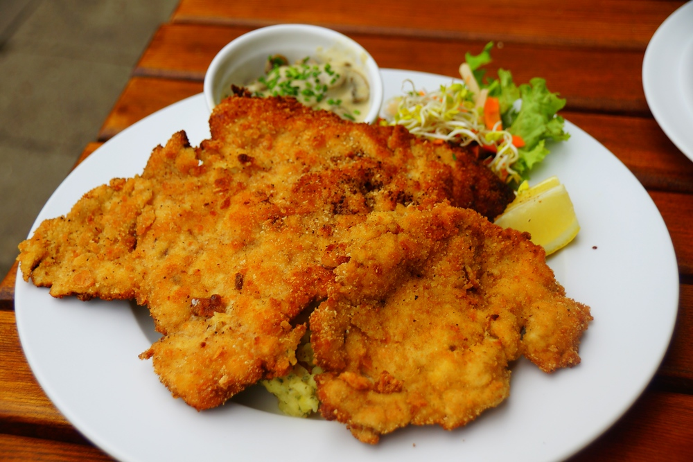 A generous portion of delicious German Schnitzel (breaded pork cutlet) for lunch on a plate in Berlin, Germany.