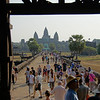 Crowds of tourists flocking towards Angkor Wat through one of the many gates.