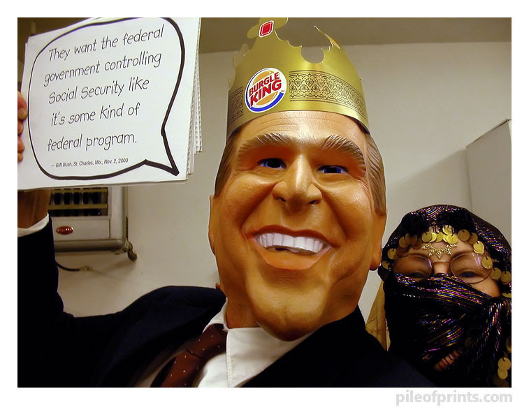 "<b>Dressed up as the ""Burgle King"" for Halloween, I held up a Bushism cartoon caption in one hand while occasionally snapping a shot of myself with the camera I held in the other hand."