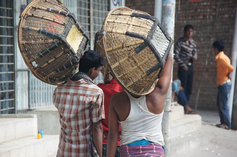A group of Bangladeshi men wander down the side walk carrying big empty baskets - Old Dhaka, Bangladesh.