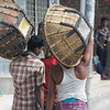 A group of Bangladeshi men wander down the side walk carrying big empty baskets - Old Dhaka, Bangladesh.