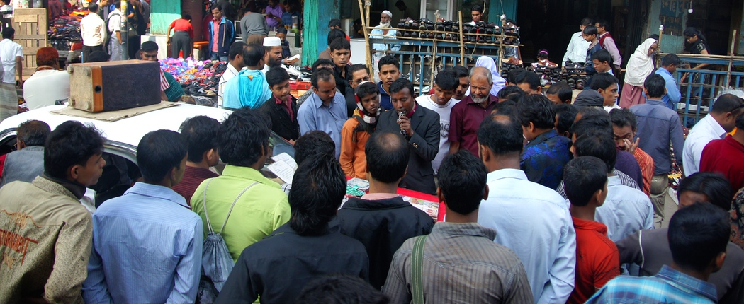 A massive crowd of local Bangladeshi men gather amidst the announcement of a street side sale - Old Dhaka, Bangladesh.