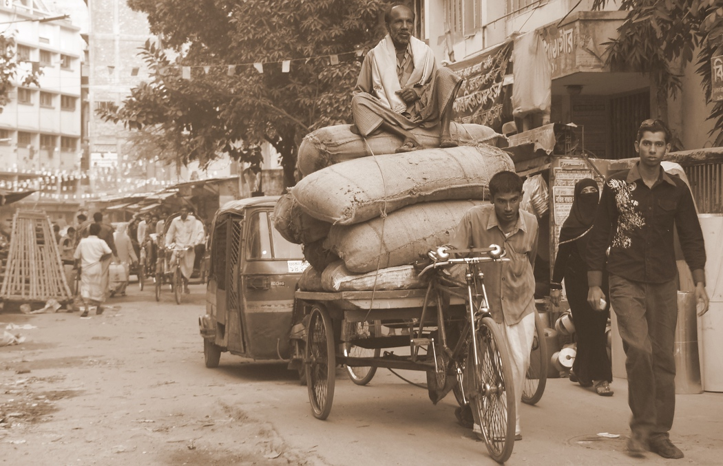 A man sits high atop of a large load on a rickshaw as a man in front of him is burdened with the task of moving everything forward.