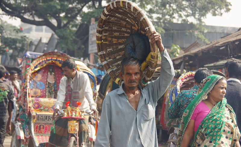 A Bangladeshi man gracefully carries an empty basket in one hand that is larger than his entire upper body - Old Dhaka, Bangladesh.