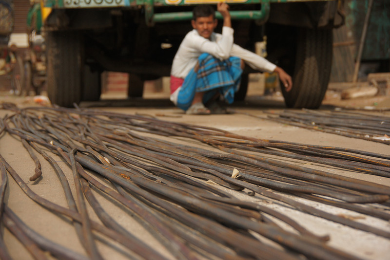 A man crouches down beside a collection of cables spread out across the ground - Old Dhaka, Bangladesh.
