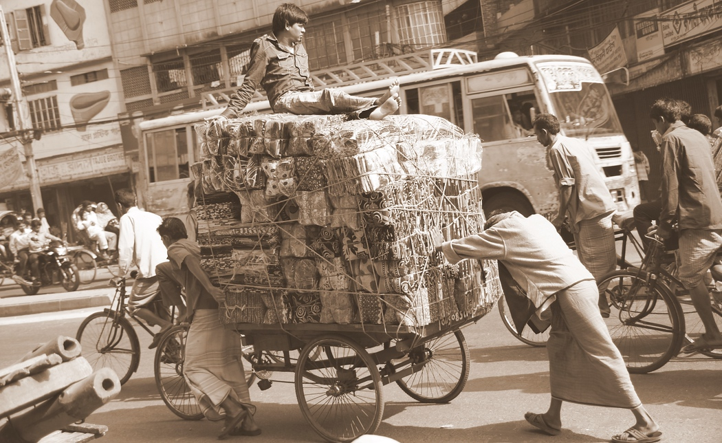 Two men push and pull a cart filled to the brim while another man sits comfortably on top of the load - Old Dhaka, Bangladesh.