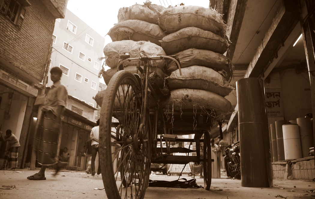 A makeshift bicycle turned into a rickshaw bares the weight of a heavy load that appears to be way beyond capacity - Old Dhaka, Bangladesh.