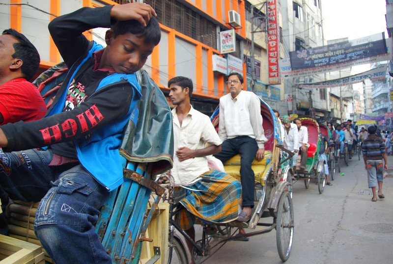 A group of men and boys were passing through this hectic section of Old Dhaka on rickshaws.  Upon careful observation one can see the endless stream of passengers.