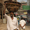 A Bangladeshi man carries a large basket on his head supported by only one arm - Old Dhaka, Bangladesh.