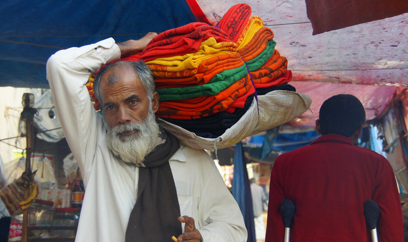 A Bangladeshi man firmly grasps a bulk collection of brightly coloured fabrics tied together in a bundle - Old Dhaka, Bangladesh.