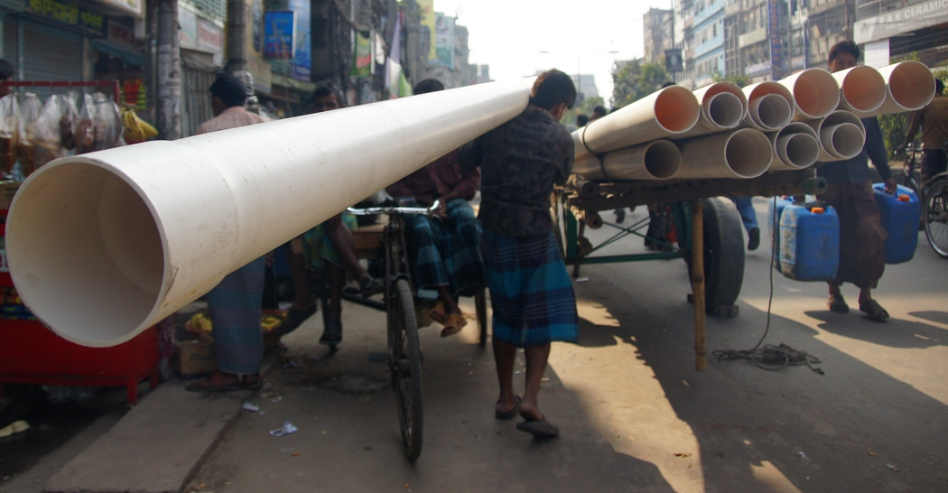 A Bangladeshi man hauls a large tube that extends well beyond the length of his body - Old Dhaka, Bangladesh.