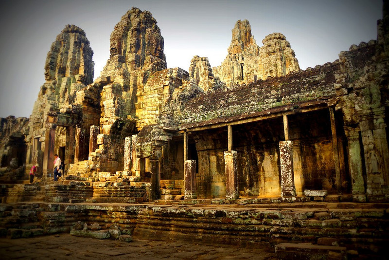 A far away vantage point angle of tourists climbing up the many steps to reach the top of Bayon.