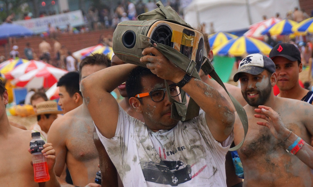A dude carrying a random 'old school' boom box entertains the wrestling crowd with music.