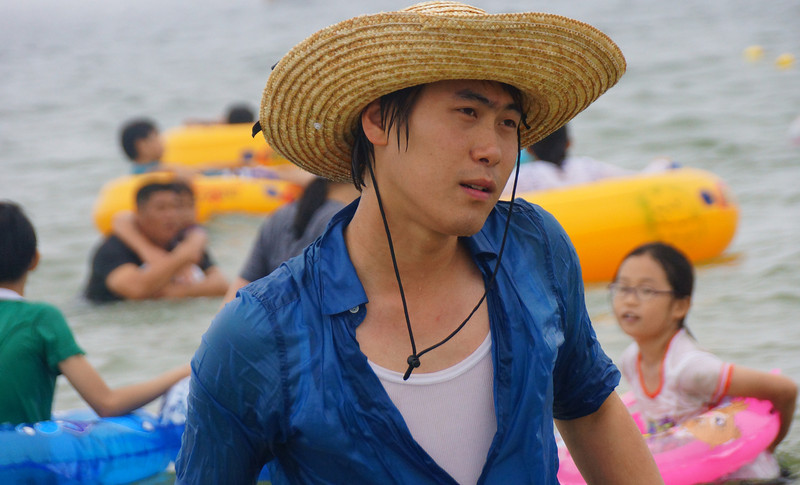A candid shot of a Korean man wearing a 'distinct' Korean style cowboy hat near the beach.