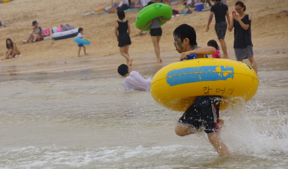 A Korean boy charges into the water with his water tube firmly gripped.