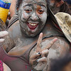 An ecstatic lady covered in mud flashes a lovely smile while posing for the camera.
