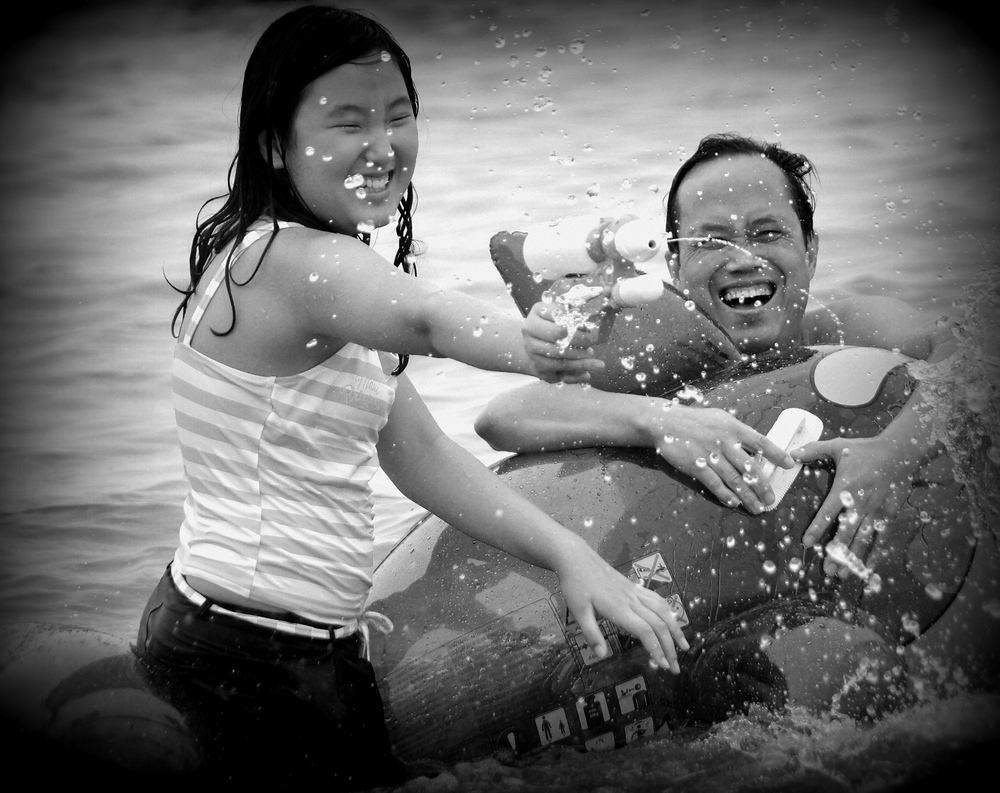 A Korean family enjoys a water gun fight with plenty of squirting and even more smiling faces.