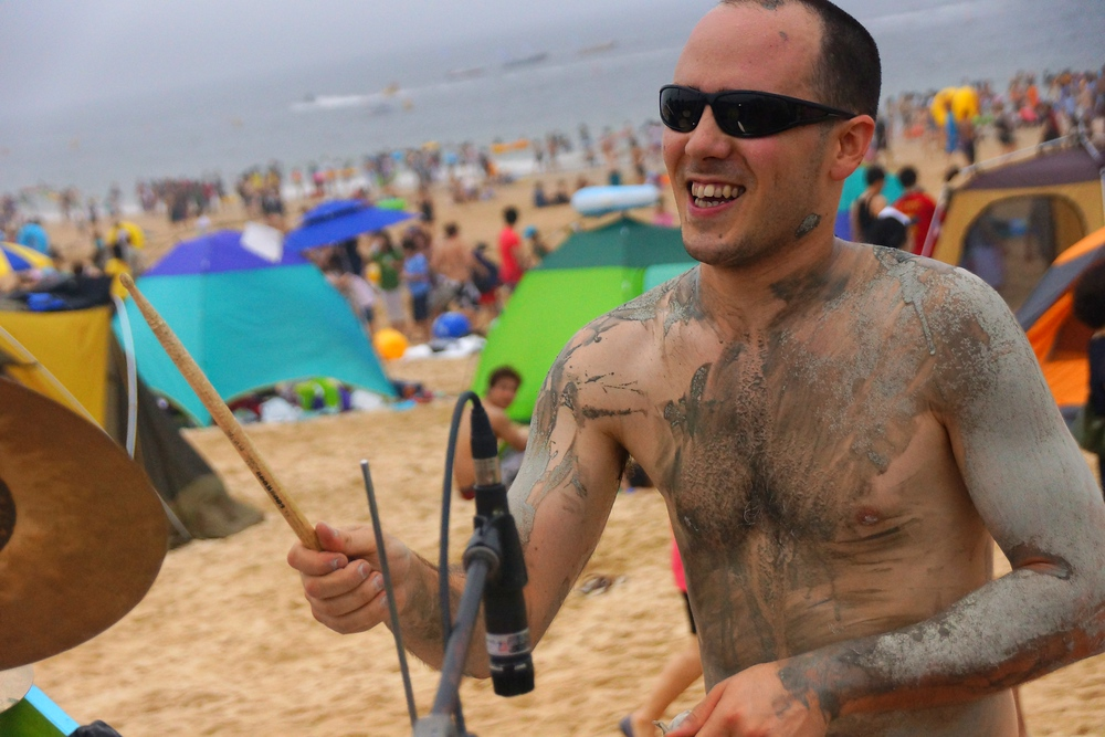A drummer plastered in mud without a shirt smiles while entertaining thousands with his slick skills.