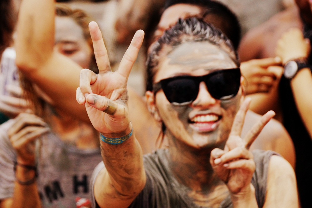 A Korean lady flashes a peace sign and an even bigger smile near the music stage.