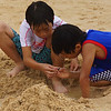Two Korean boys enjoying digging sand in what appears to be an early foundation of a sandcastle.