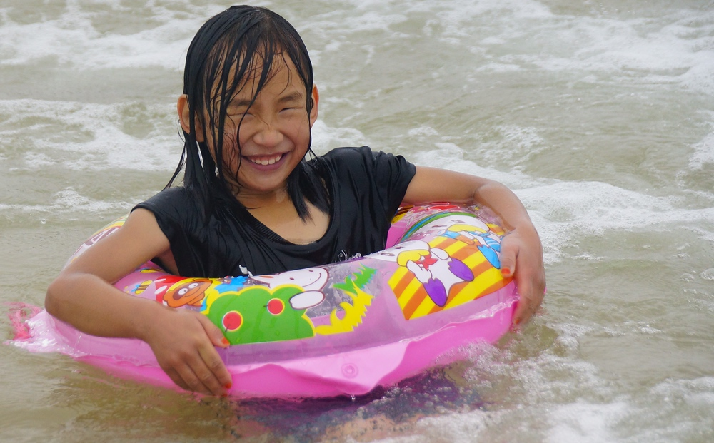 A Korean flashes an authentic smile while enjoying a moment splashing around in a floating tube at Daecheon Beach, Korea.