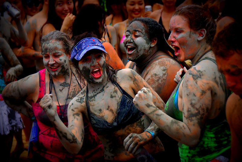 A group of women cheer each other on as they dance during the Boryeong Mud Festival.