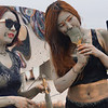Two Korean girls paint themselves with mud nearby Daecheon beach.