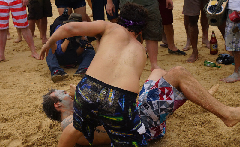 Two foreigners wrestle on the beach and one is clearing winning this match with a serious take-down.
