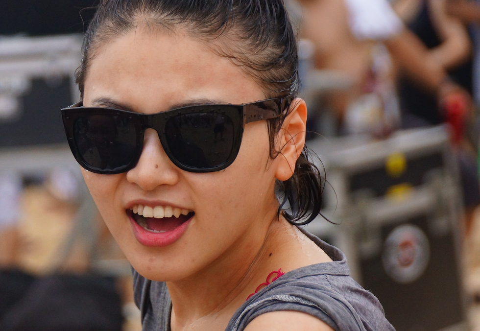A candid smile from a Korean girl wearing shades and rocking out to the bands playing at the stage.