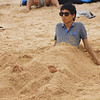 A Korean man is buried in sand yet looks surprising chilled out and relaxed on the beach.