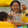 A cute Korean girl wearing red glasses poses for the camera, flashes a smiling face and appears genuinely happy in the water.