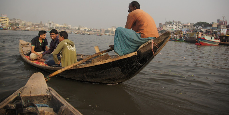 "The rowboat you see in front of us is nearly identical to the one I've just boarded:<br /> <a href=""http://nomadicsamuel.com/photo-essays/boat-buriganga-sadarghat-dhaka-bangladesh"">http://nomadicsamuel.com/photo-essays/boat-buriganga-sadarghat-dhaka-bangladesh</a>"