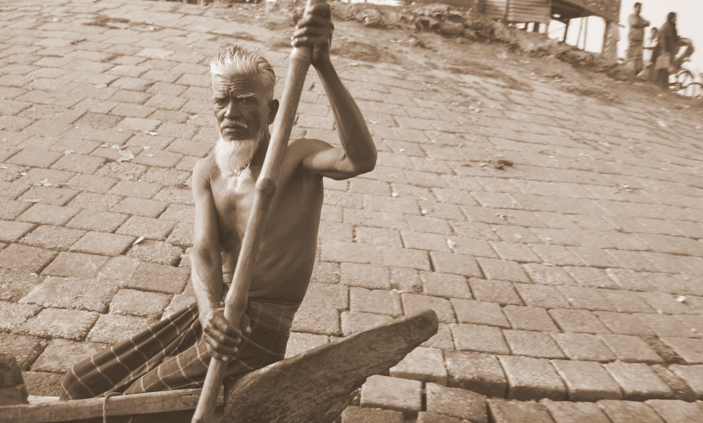An oarsman with a stern face and white beard glares at me as we pass his vessel.