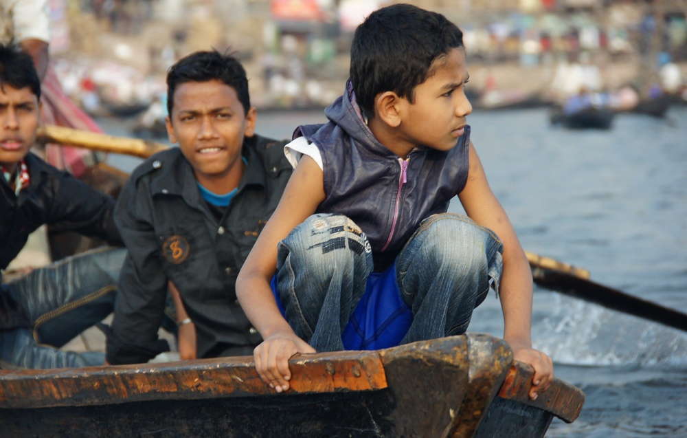 A close-up telephoto shot of a group of young Bangladeshi boys/teenagers on a small river boat plying the waters of the Buriganga.