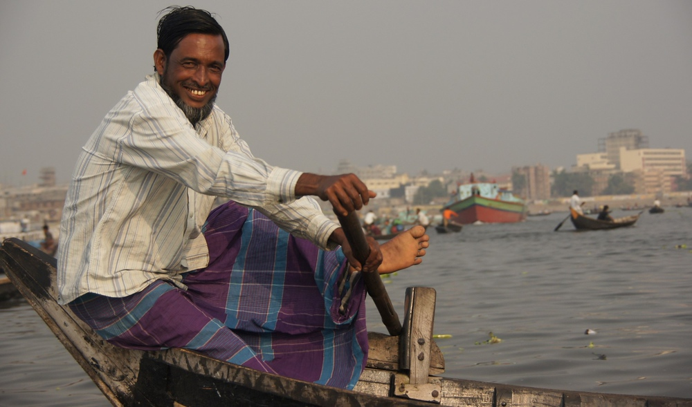 A Bangladeshi man, an oarsman on a small vessel, flashes a wonderful radiant smile; one of many smiles that would make my day.