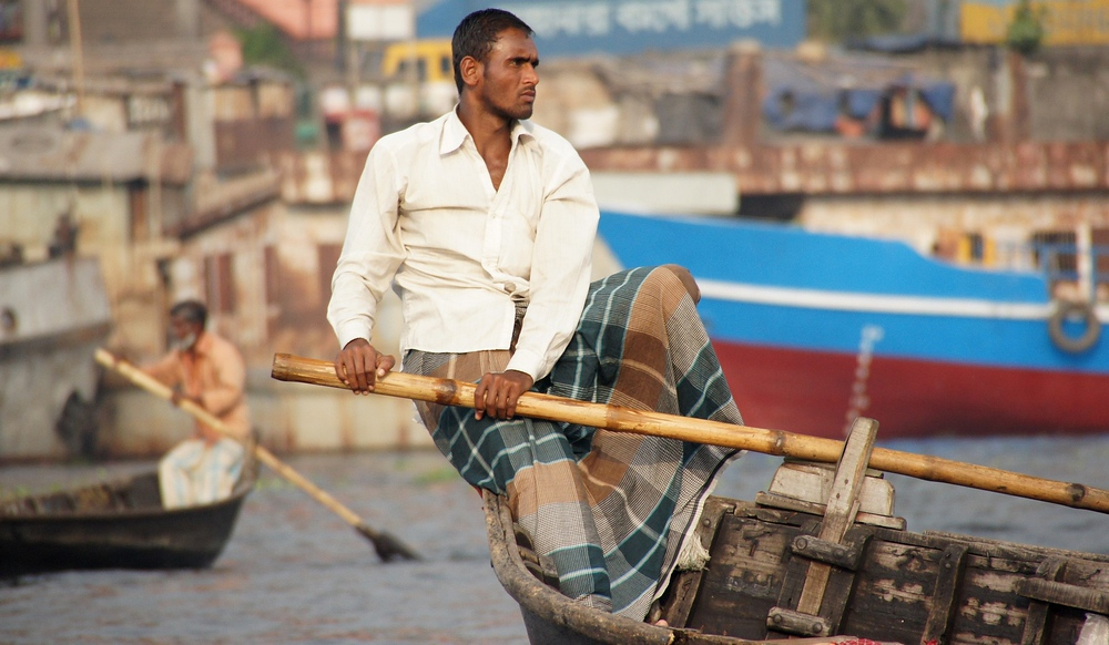 The button down shit and lungi (Bangladeshi skirt for men) are typical attire for Bangladeshi men - especially the oarsmen.